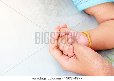 Mother's hand cradles the hand of a baby background for love and mothers day.