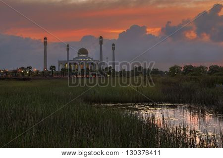 Beautiful mosque on green field with sunset and reflection