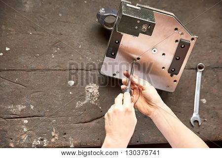 A working woman hands using a screwdriver.