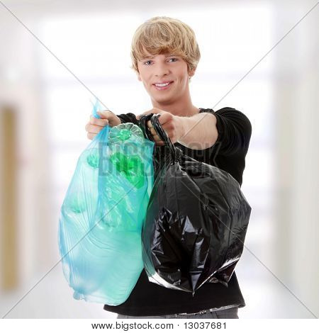 Young man carrying a plastic trash bags full with empty recyclable household material.