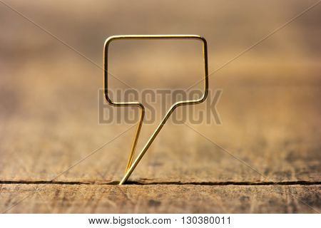 Golden tweet or remark. Blank speech bubble made of gold wire on rustic or grunge wood ready for inserting text. Shallow depth of field.