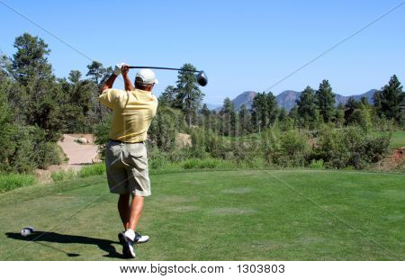 Golfer Teeing Off In The Mountains Over A Hazard