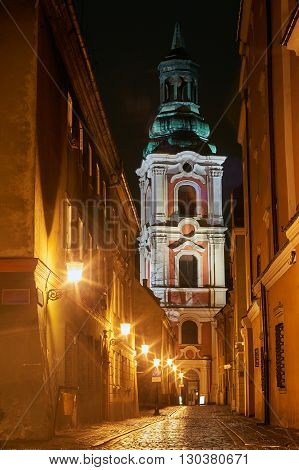 A church and cobbled street at night in Poznan