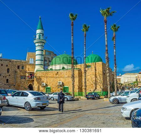 ACRE ISRAEL - FEBRUARY 20 2016: The old stone E-Zaitune Mosque with the white minaret and bright green domes located next to the Turkish Bazaar on February 20 in Acre.