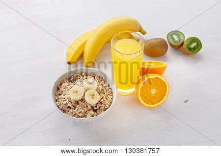 Granola bananas glass of orange juice and kiwi on a light wooden surface. Healthy food