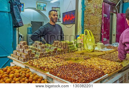 ACRE ISRAEL - FEBRUARY 20 2016: The merchant in Turkish bazaar offers the tasty nuts' gozinaki lokum halva and other desserts on February 20 in Acre.