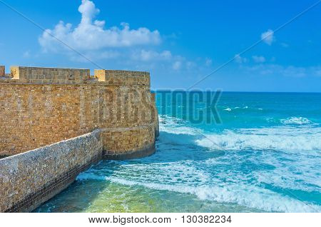 The waves beat against the stone sea wall of the fortress of Acre Israel.
