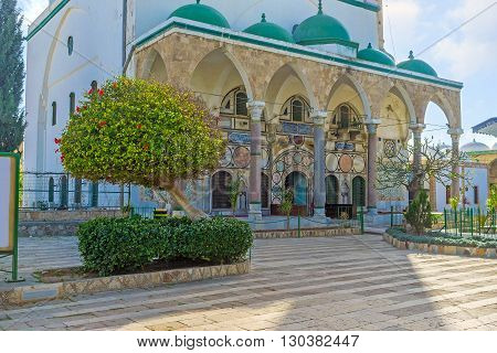 The beautiful facade of Al-Jazzar mosque with blooming trees of local garden Acre Israel.