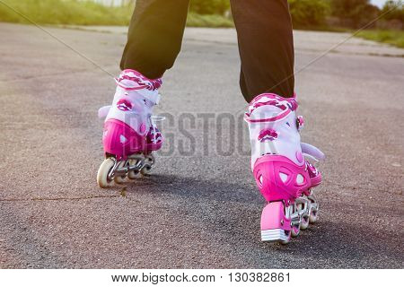 The legs of a young girl as she is rollerblading on a sunny day