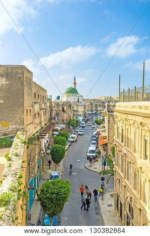 ACRE ISRAEL - FEBRUARY 20 2016: The narrow Salah Al-Din street leads from the city gates to the center with the rising Al-Jazzar mosque on background on February 20 in Acre.