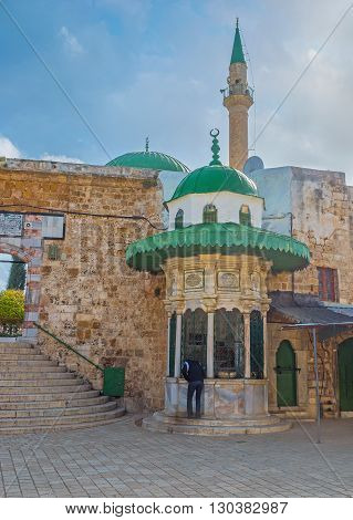The central entrance to Al-Jazzar mosque with white sabil built in rampart Acre Israel.