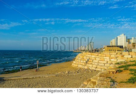 TEL AVIV ISRAEL - FEBBRUARY 25 2016: The seashore with the narrow Alma beach line and modern high-rises on the background on February 25 in Tel Aviv.