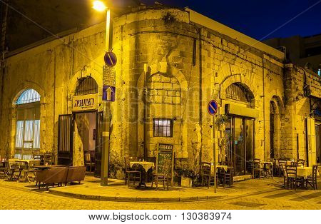 TEL AVIV ISRAEL - FEBBRUARY 25 2016: The outdoor cafe occupies the medieval house corner especially scenic in the evening on February 25 in Tel Aviv.
