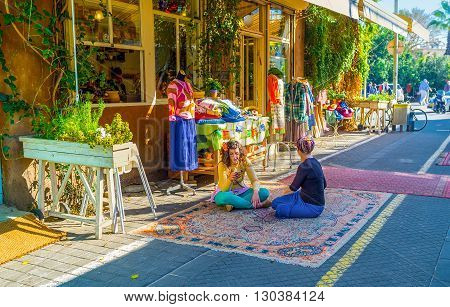 TEL AVIV ISRAEL - FEBRUARY 25 2016: The sellers from the clothes workshop sit cross-legged on the rug in market street of old Jaffa on February 25 in Tel Aviv.