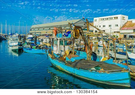TEL AVIV ISRAEL - FEBBRUARY 25 2016: The old fishing boats in port of Jaffa attract the tourists here to enjoy the views and taste local cuisine in one of taverns on February 25 in Tel Aviv.