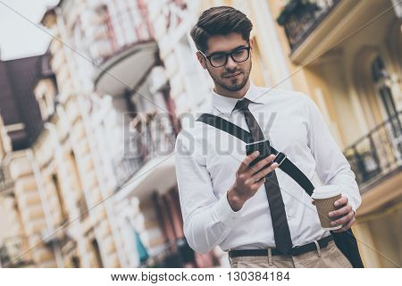 Coffee break on a go. Low angle view of confident young man in glasses holding coffee cup and using his smart phone while walking outdoors
