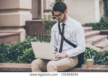 Technologies make life easier. Confident young man in glasses using his laptop while sitting outdoors
