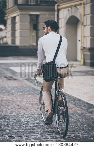 On the way to work. Rear view of young man in glasses looking away while riding his bicycle