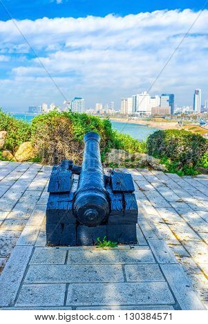 The old black cannon on the Jaffa hill with the modern Tel Aviv buildings on background Israel.