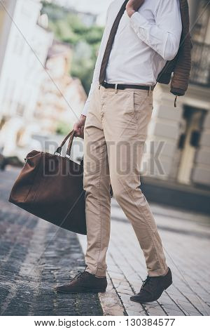 Trendy look. Part of man holding leather bag while walking outdoors
