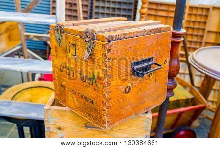 TEL AVIV ISRAEL - FEBRUARY 25 2016: The old wooden box with the hebrew inscriptions in the flea market stall on February 25 in Tel Aviv.