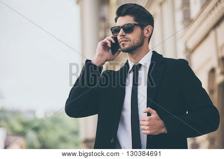 Important call. Handsome young well-dressed man talking on mobile phone and looking away while standing outdoors