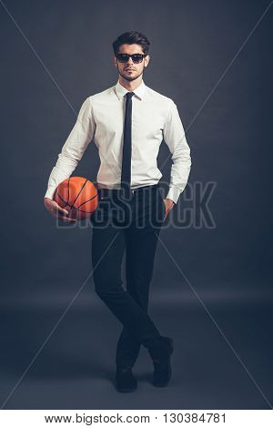 Ready to play? Full length of handsome well-dressed young man  holding basketball ball and looking at camera while standing against grey background