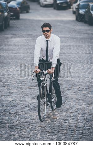 Ride it. Full length rear view of handsome well-dressed young man riding his bicycle outdoors