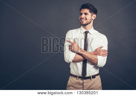 Take a look here! Confident young handsome man pointing at copy space with smile while standing against grey background