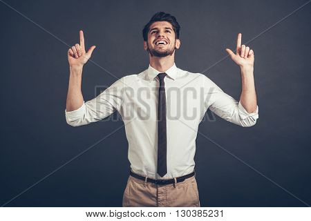 Look up! Confident young handsome man pointing up at copy space with smile while standing against grey background