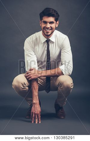 Can you resist his smile? Full length of confident young handsome man looking at camera with smile while sitting crouched against grey background
