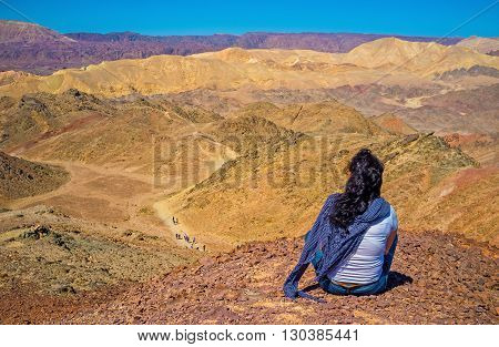 The girl relaxes after the hiking sitting on peak of Zefahot Mount and watch the amazing colorful landscapes Eilat Israel.