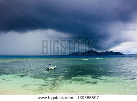 Tropical storm over an island, motor boat