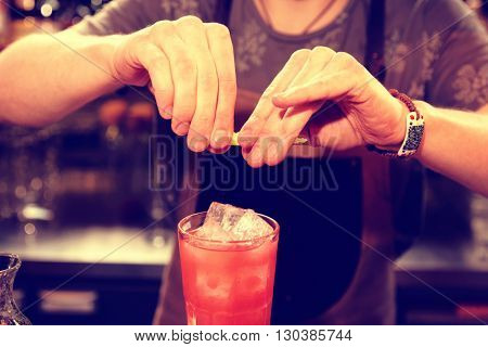 Bartender is adding zest oil to the cocktail, toned image