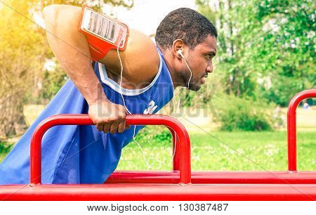 African american man sport exercise listening music with earphones at city park - Black handsome guy workout triceps session outdoors - Concept of strength determination and healthy lifestyle