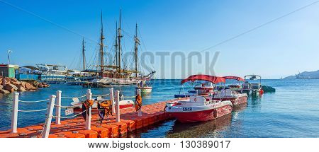 EILAT ISRAEL - FEBRUARY 23 2016: The small speedboats for the incredible sightseeing experience and the large wooden sailing ships for the romantic voyages on February 23 in Eilat.