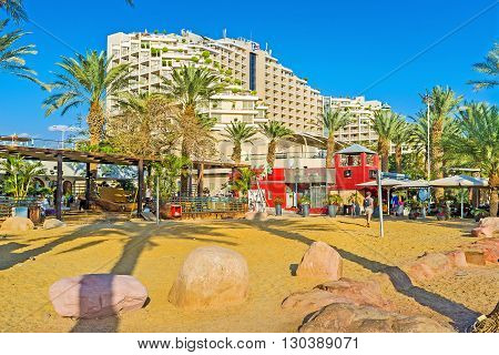 EILAT ISRAEL - FEBRUARY 23 2016: The sand beach surrounded by summer cafes and bars offering fresh beverages on February 23 in Eilat.