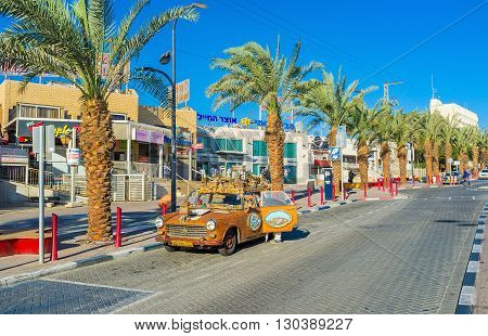 EILAT ISRAEL - FEBRUARY 24 2016: The tourist car decorated with the model of the medieval town-fortress and colorful reliefs on February 24 in Eilat.