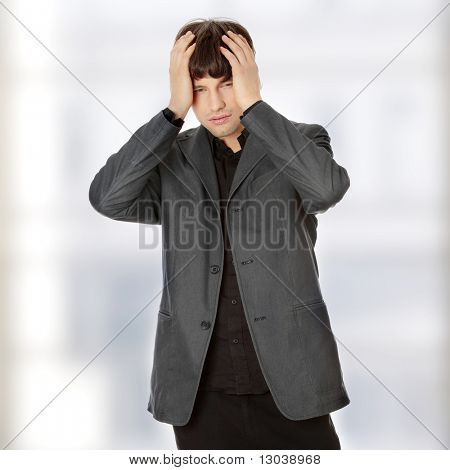 Young businessman with a big headache or problem