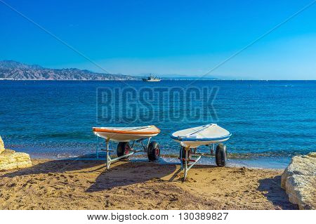 The beautiful seascape with two surfboards on trailers on the background Eilat Israel.
