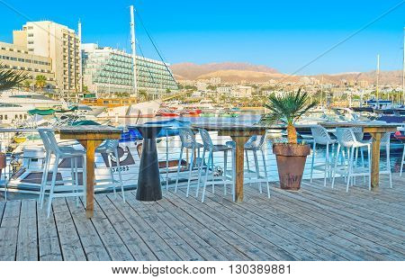 EILAT ISRAEL - FEBRUARY 23 2016: The cozy outdoor cafe on the wooden terrace in marina with the view on the white yachts on February 23 in Eilat.