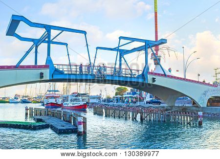 EILAT ISRAEL - FEBRUARY 23 2016: The modern drawbridge over the entrance to the marina with the yachts and pleasure boats on the background on February 23 in Eilat.