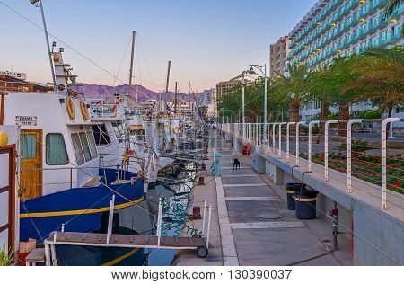 EILAT ISRAEL - FEBRUARY 23 2016: The evening promenade along the moored yachts in port on February 23 in Eilat.