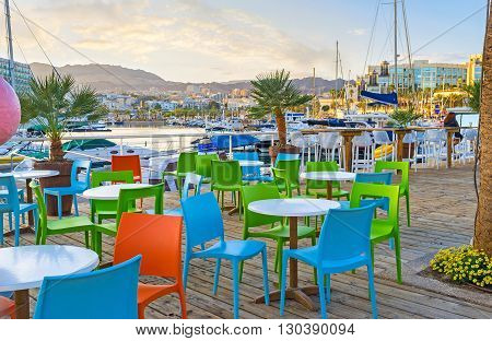 The scenic outdoor cafe in Lagoona of Eilat with the picturesque view on the moored yachts green palms and the mountains in the sunset lights Israel.