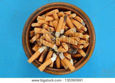 cigarette filter in ceramic ashtray on blue desk