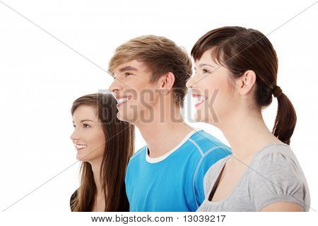 Three young happy friends. Two girls one boy smiling and looking left. Focus on male. Isolated on white background.