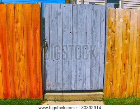 Perfect new fence with ugly painted gray door of fence peaking through in Cleveland, Ohio.