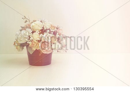 Artificial flowers in flowerpot on wooded background.Artificial flowers with vintage style effect.