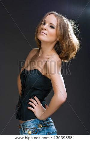 Sexy beautiful young woman posing on bark background, looking at camera. Winking Girl  in jeans and black fashionable top. Studio shot.