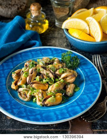 A delicious blue mussel salad with parsley green onion olive oil white wine and lemon.